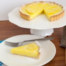 A slice on lemon tart on a plate