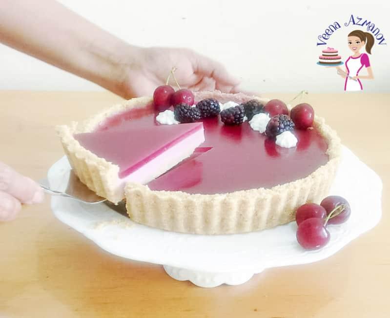 A blackberry Panna Cotta tart on a cake stand.