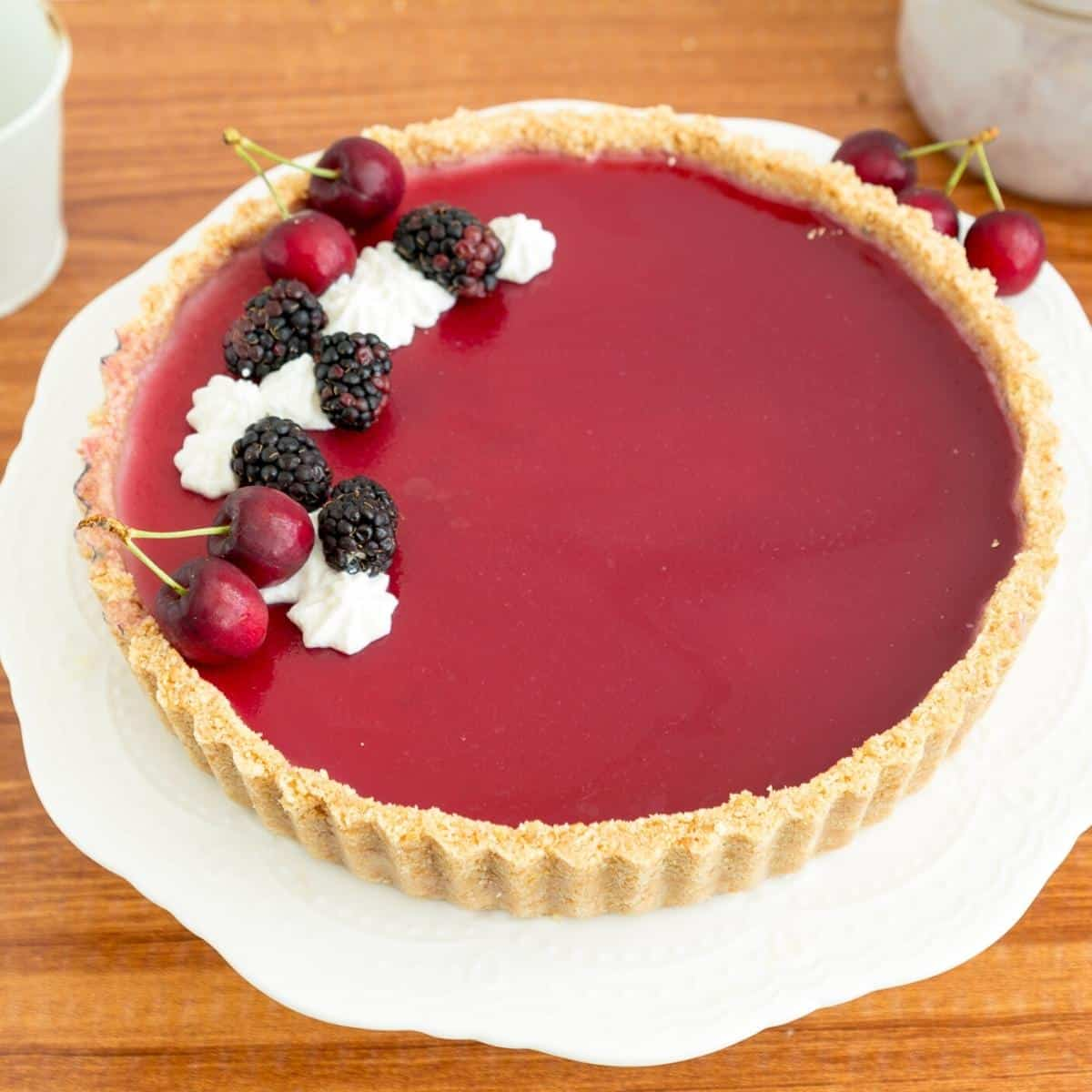 Panna cotta tart with blackberries on a cake stand.