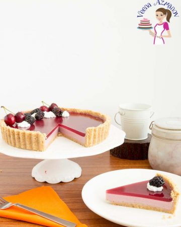 A blackberry Panna Cotta tart on a cake stand.