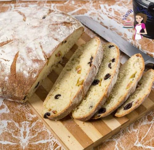 A sliced beer bread with olives on a cutting board.