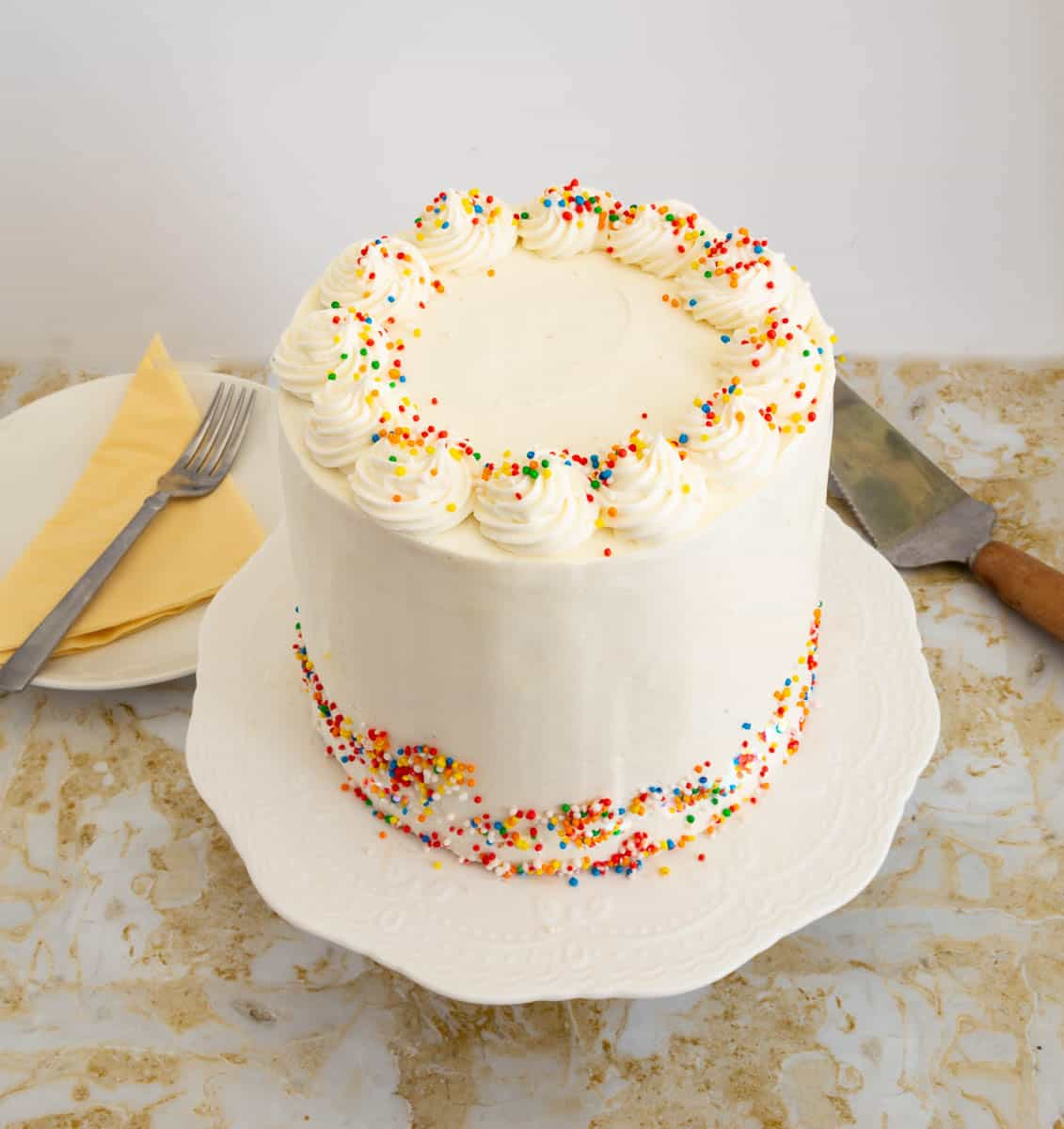 Frosted vanilla birthday cake on a cake stand