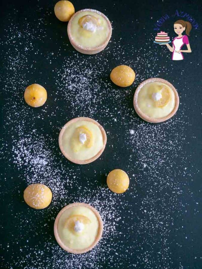 A top view of mini lemon tarts on a table.