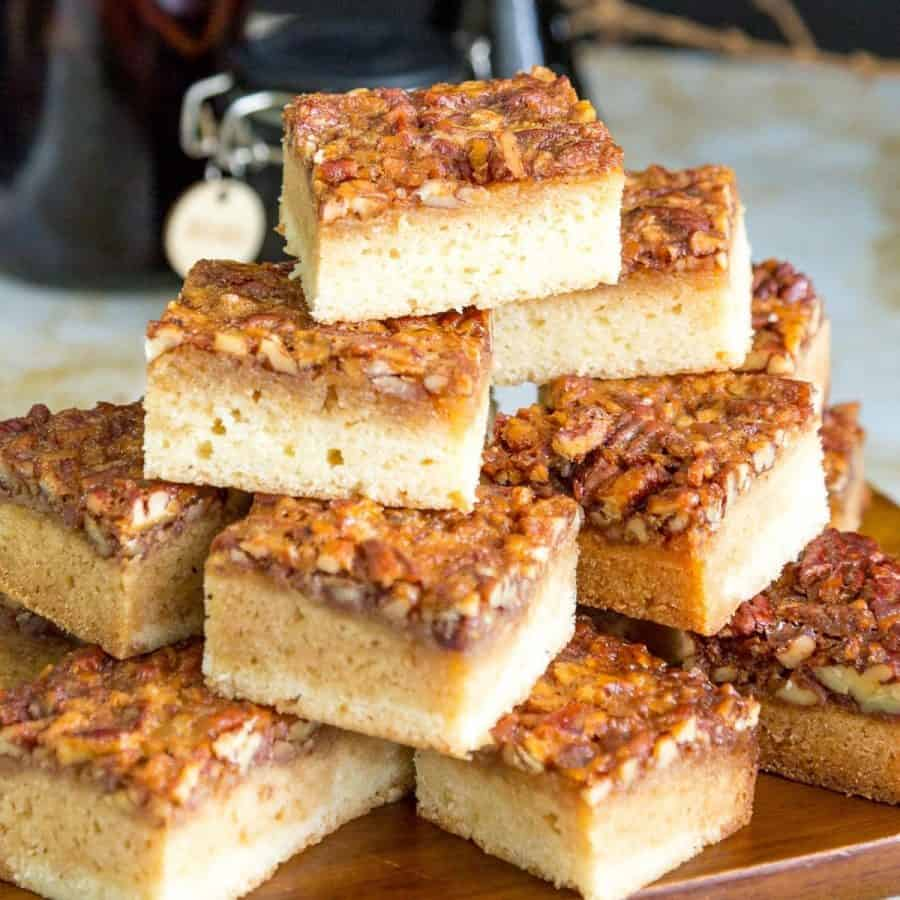 Stack of pecan blondies on a wooden board