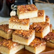 Blondies stacked on a wooden board.