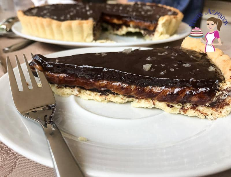 A slice of caramel chocolate tart on a plate.