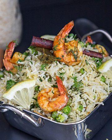 Shrimps over rice in a skillet.