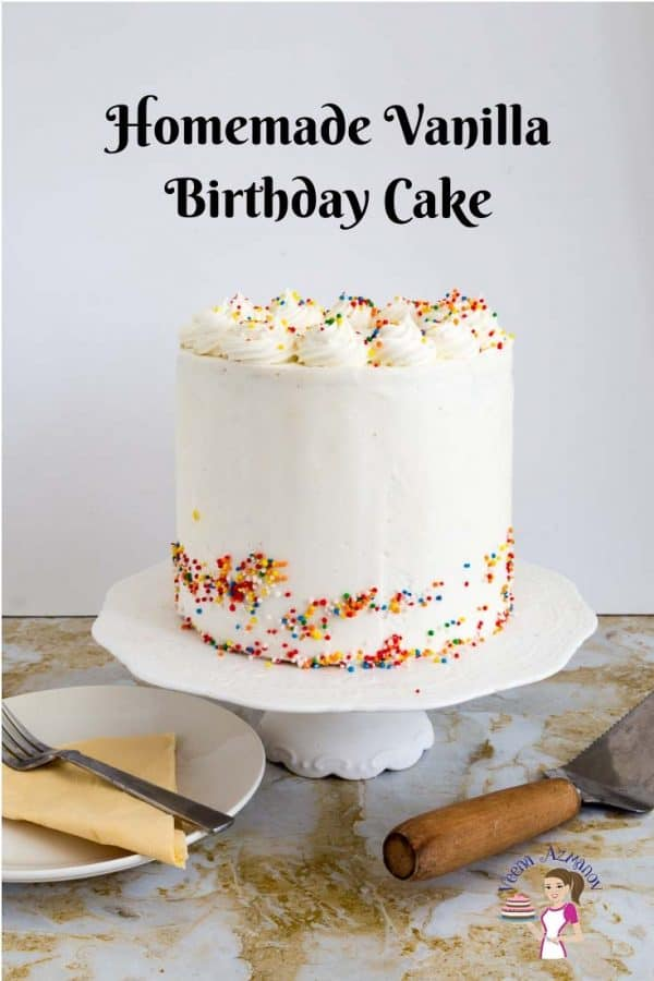 A birthday cake with white frosting on a cake stand.