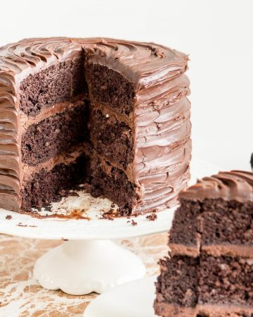 A sliced chocolate cake on a cake stand.