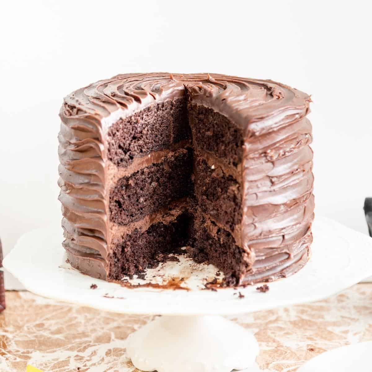 A sliced chocolate cake on cake stand.