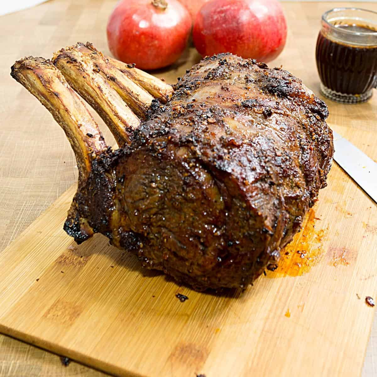 A roasted standing rib on a wooden board.
