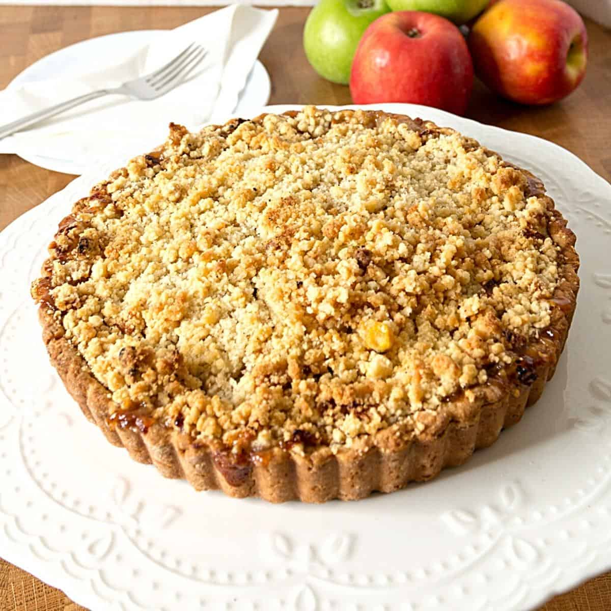 Apple crumble pie on a cake stand.