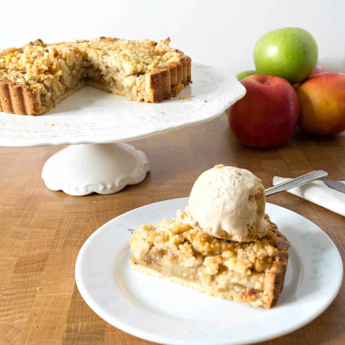 A slice of apple crumble tart on a plate.