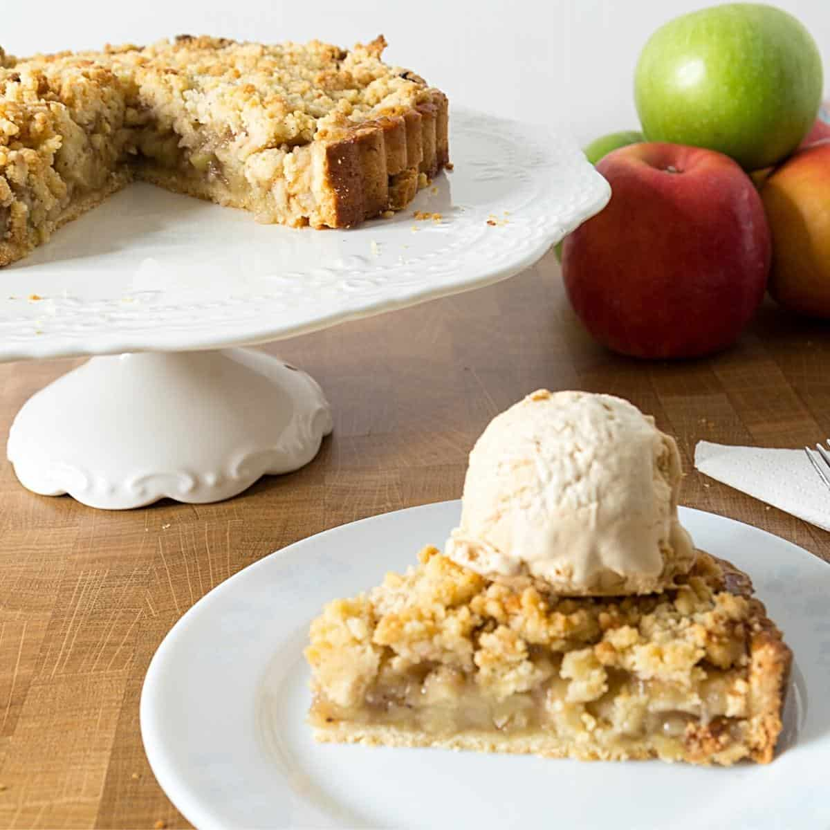 A slice of crumble tart topped with ice cream.