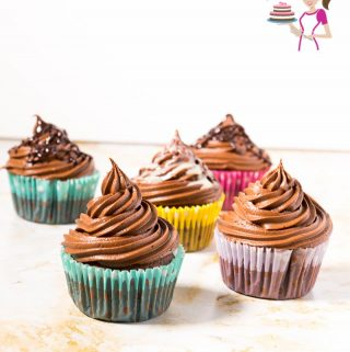 Chocolate cupcakes with Chocolate frosting on a table.