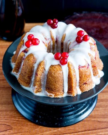 A bundt cake with fresh cranberries on cake stand.