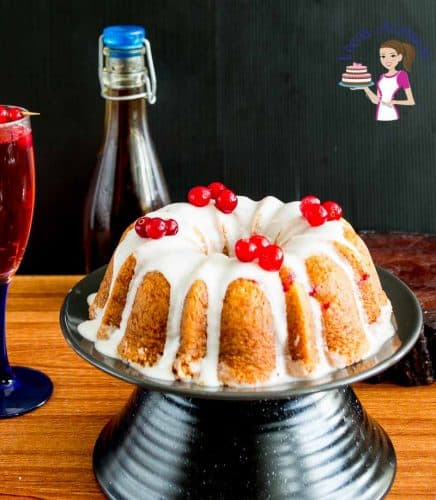 A cranberry cream cheese pound cake on a cake stand.