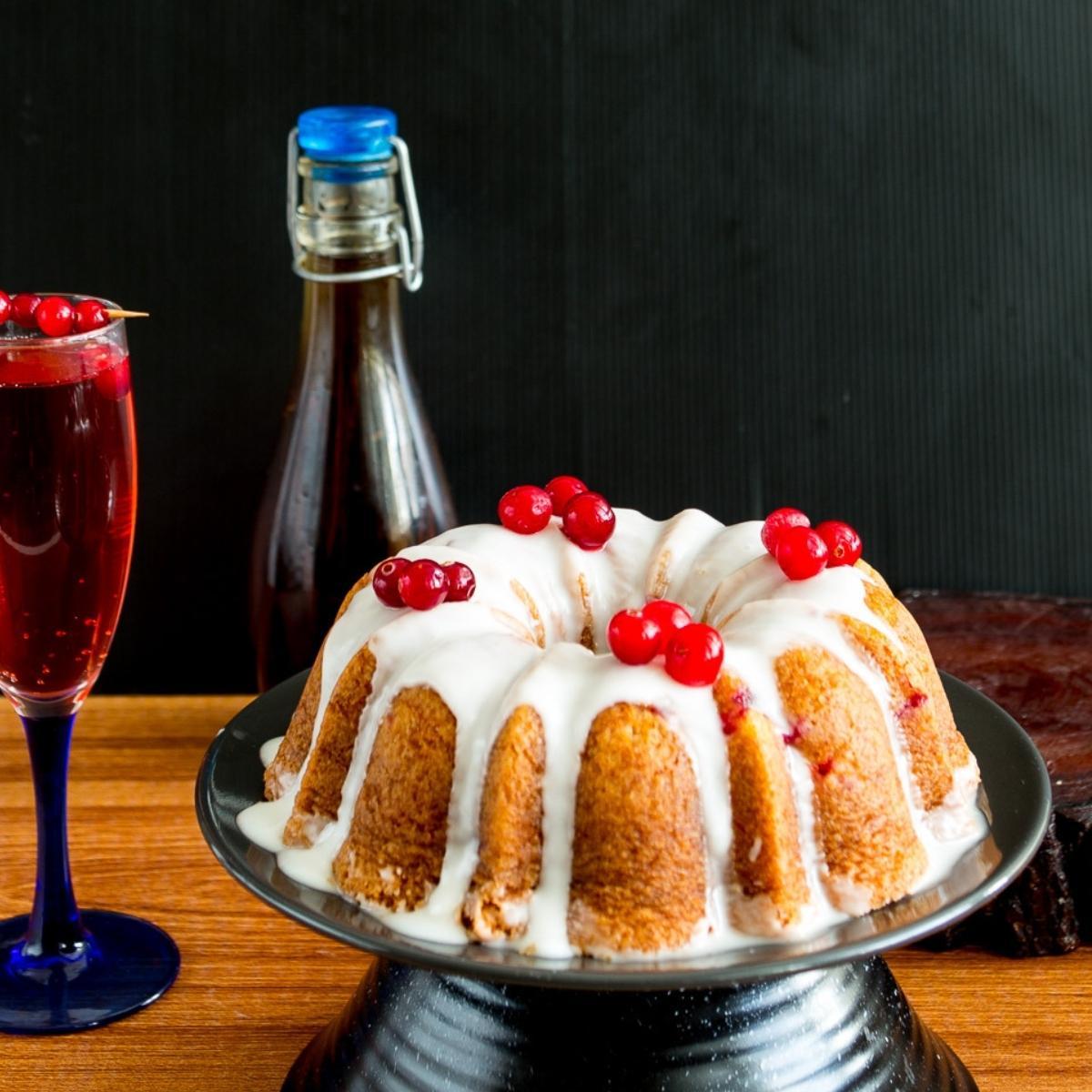 A cranberry bundt cake on a cake baord