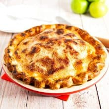 A pie in a pie pan with granny smith apples.