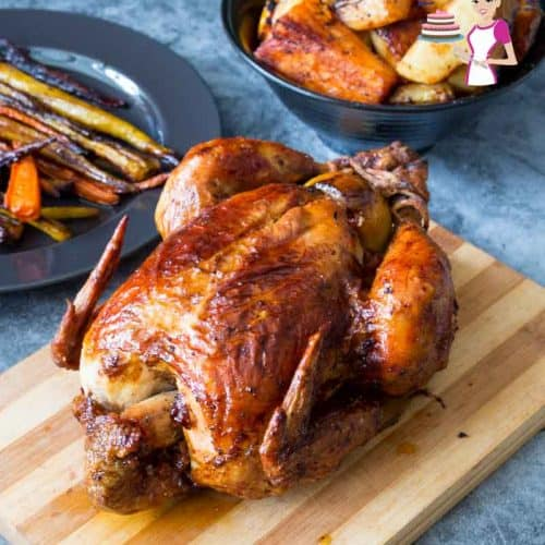 Whole roasted chicken on a wooden board.