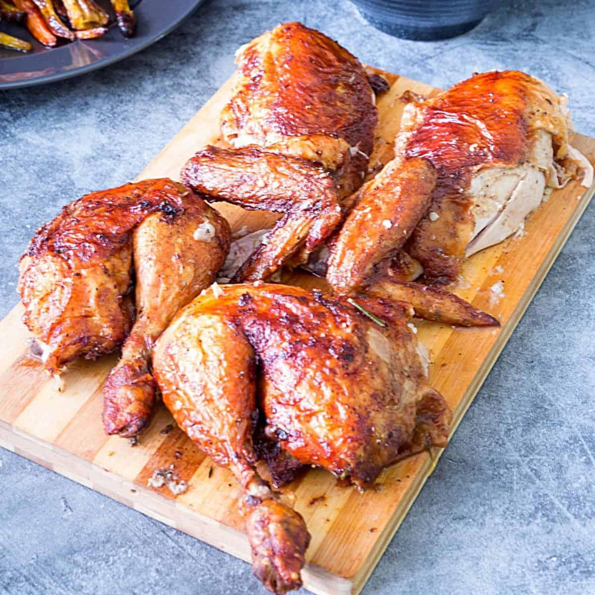A cut roasted chicken on a wooden board.