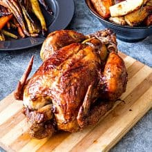 A roasted chicken on a wooden board.