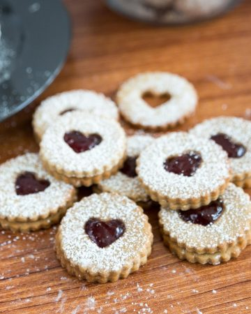 jam Linzer cookies on a wooden table