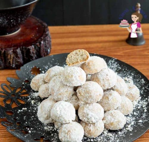A stack of snowball cookies on a plate.