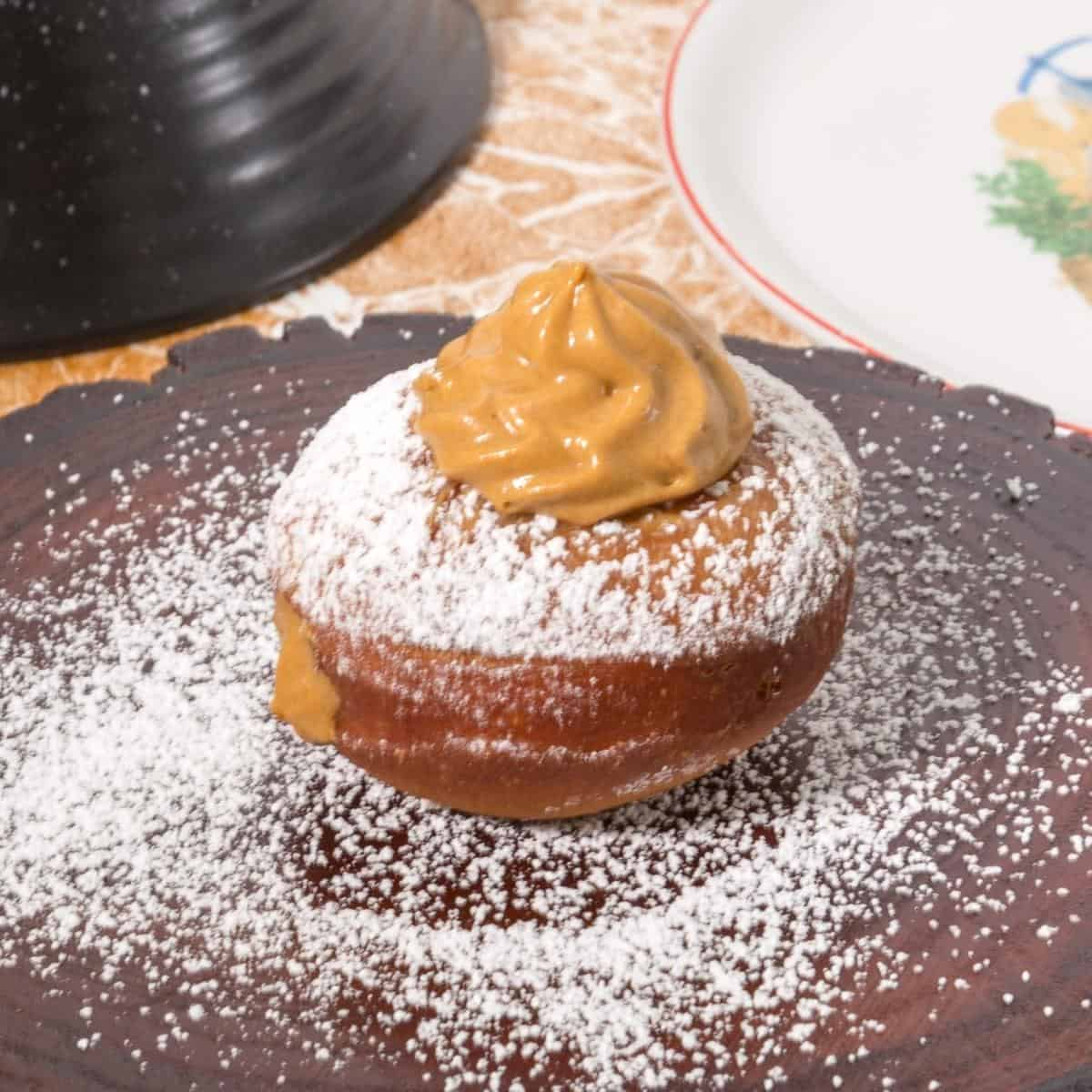 A doughnut topped with dulce de leche cream