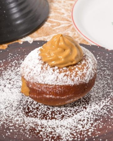 One doughnut on a wooden board topped with dulce de leche cream