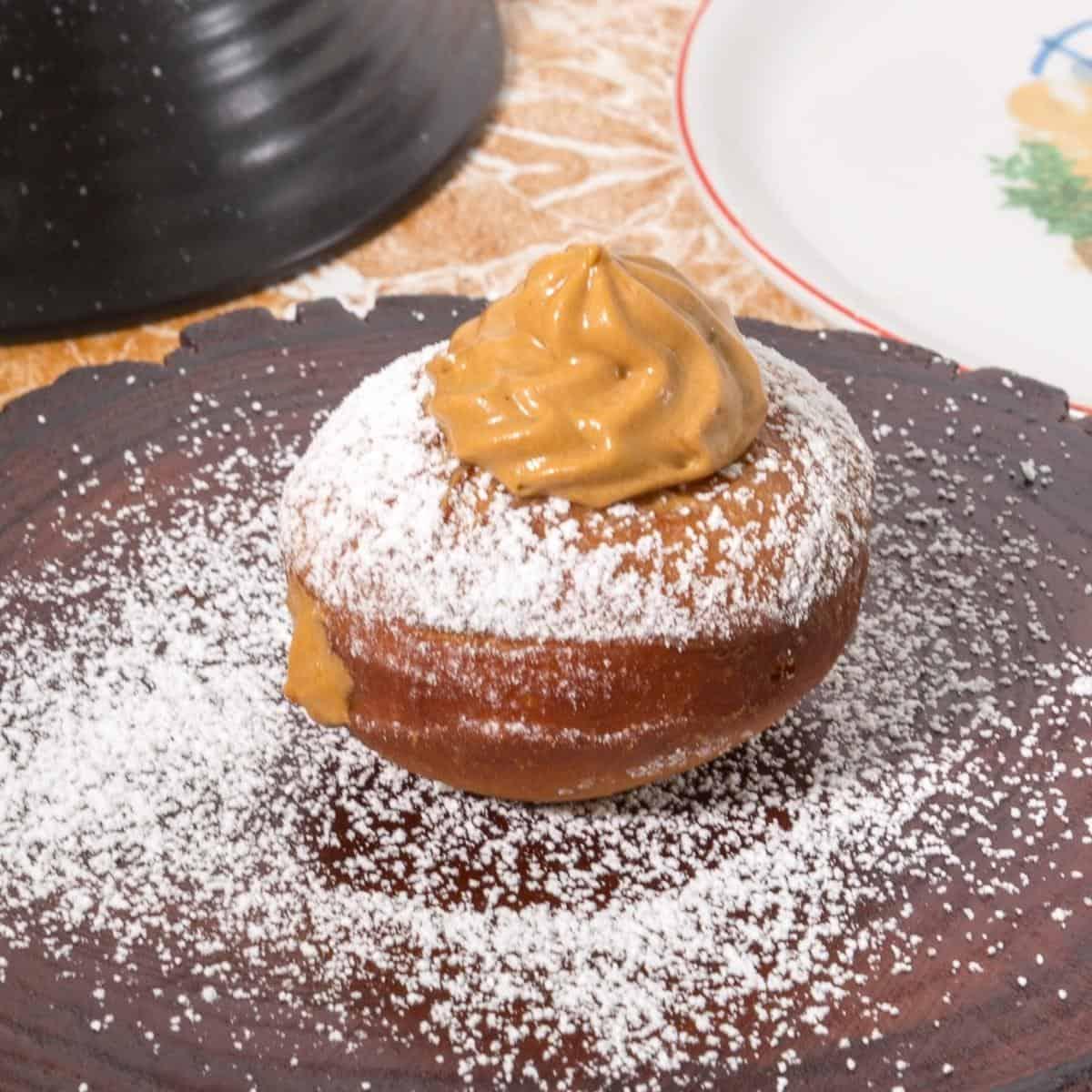 Dule de leche donut on a wooden baord