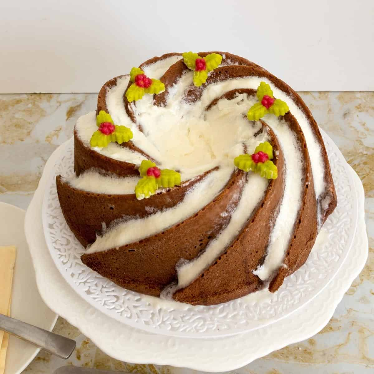 A frosted bundt cake on a cake stand
