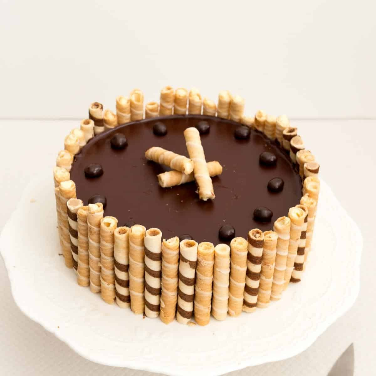 A glutenfree chocolate cake with wafers on cake stand.