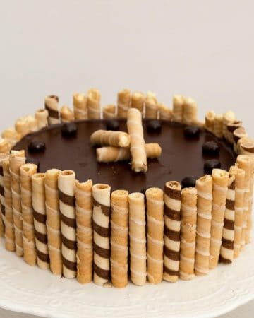 A flourless chocolate cake with wafers on a cake stand.