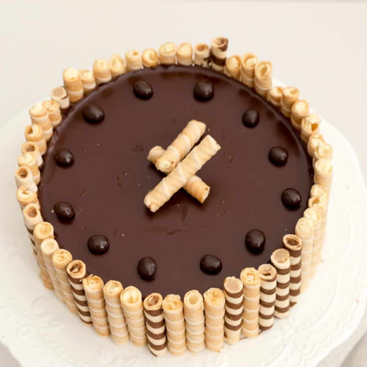 Flourless chocolate cake with chocolate wafers on a cake stand.