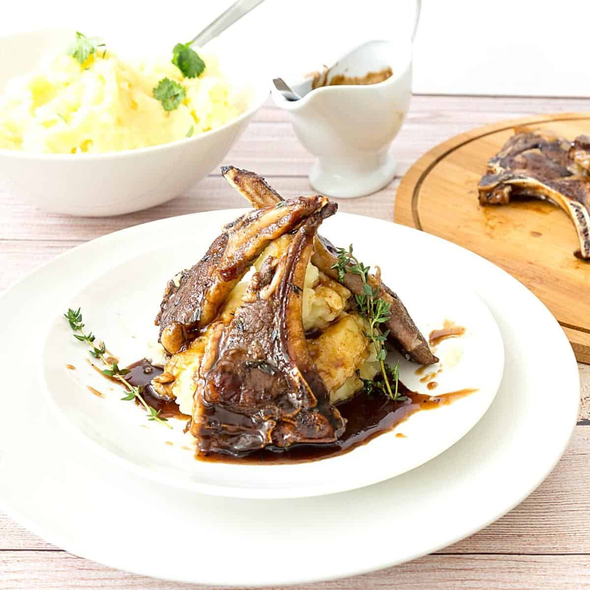 A plate with mashed potatoes and lamb chop with balsamic sauce.
