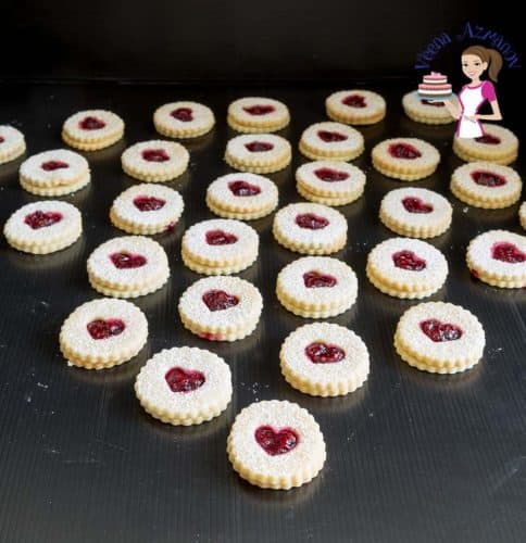 Raspberry Linzer cookies arranged on a table.