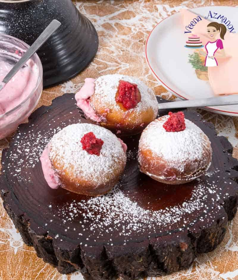 Three raspberry cream filled donuts on a wooden stand.