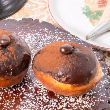 Two tiramisu donuts on a wooden baord