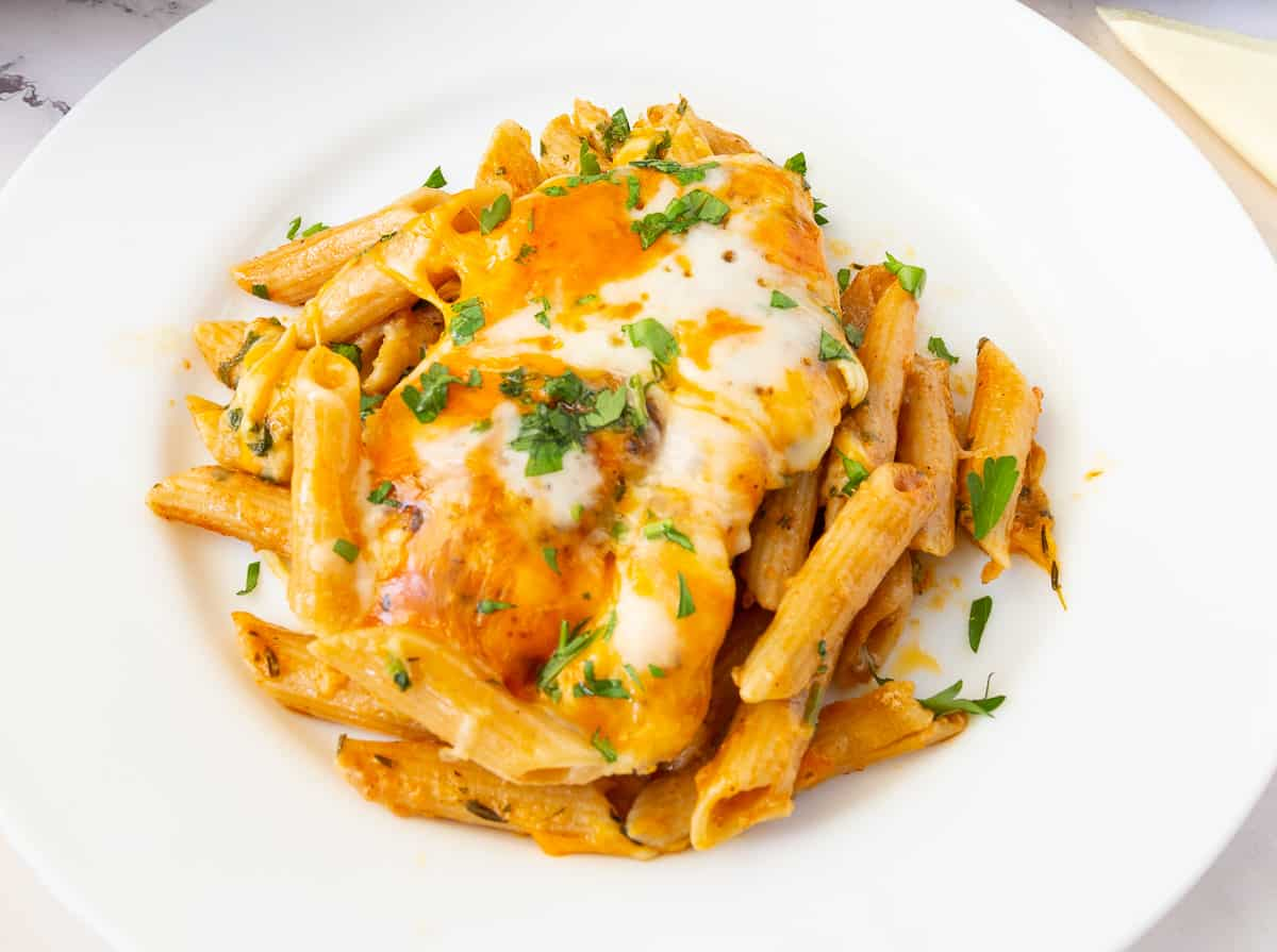 A plate served with chicken and pasta.