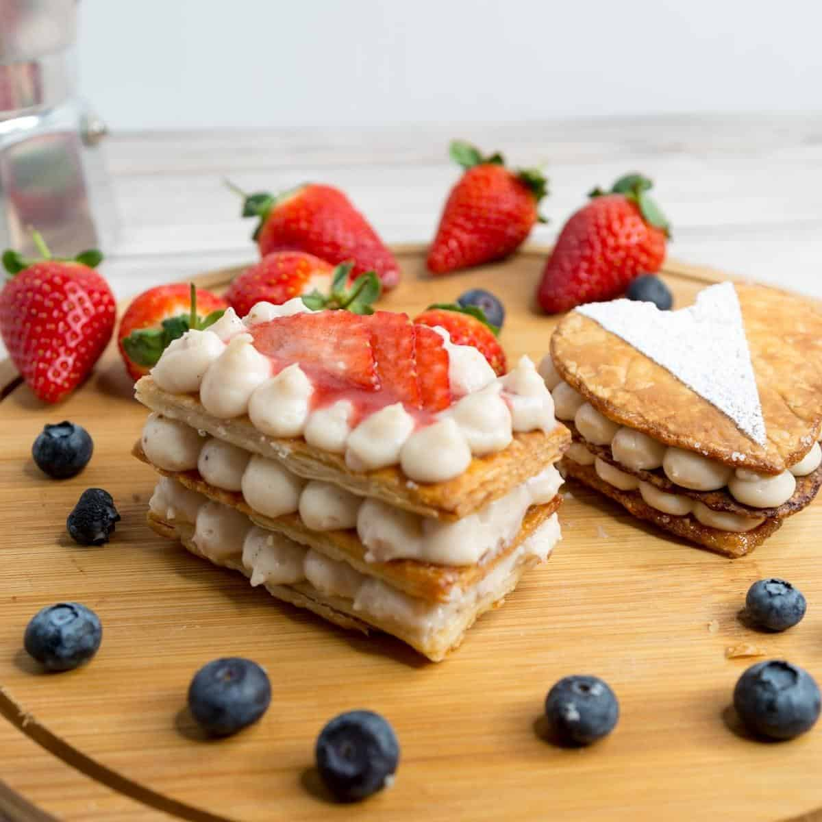 Two Mille Feuille on a wooden board with fruits