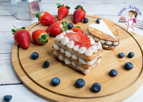 A piece of strawberry Mille-feuille on a wooden tray.