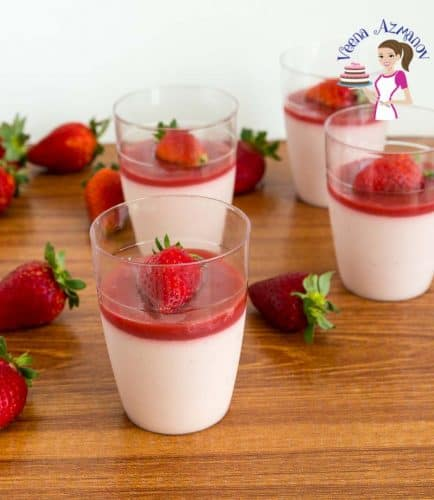 Strawberry Panna cotta in a serving glass on a wooden board.
