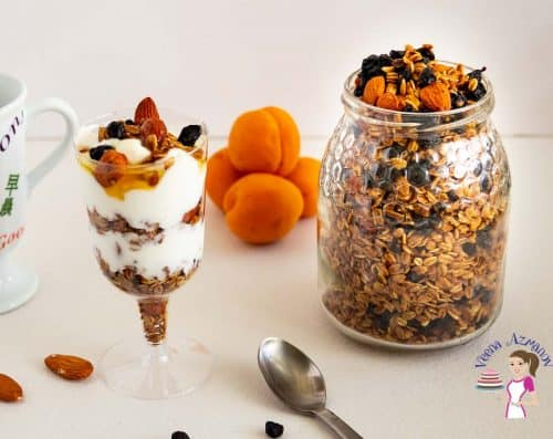 A jar with homemade granola and blueberries next to a glass with yogurt and granola parfait.