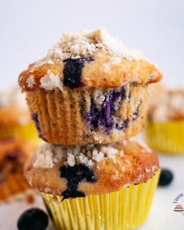 Two blueberry muffins, one on top of the other.