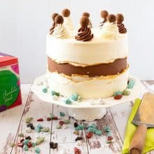 A frosted cake with fault line on a cake stand.