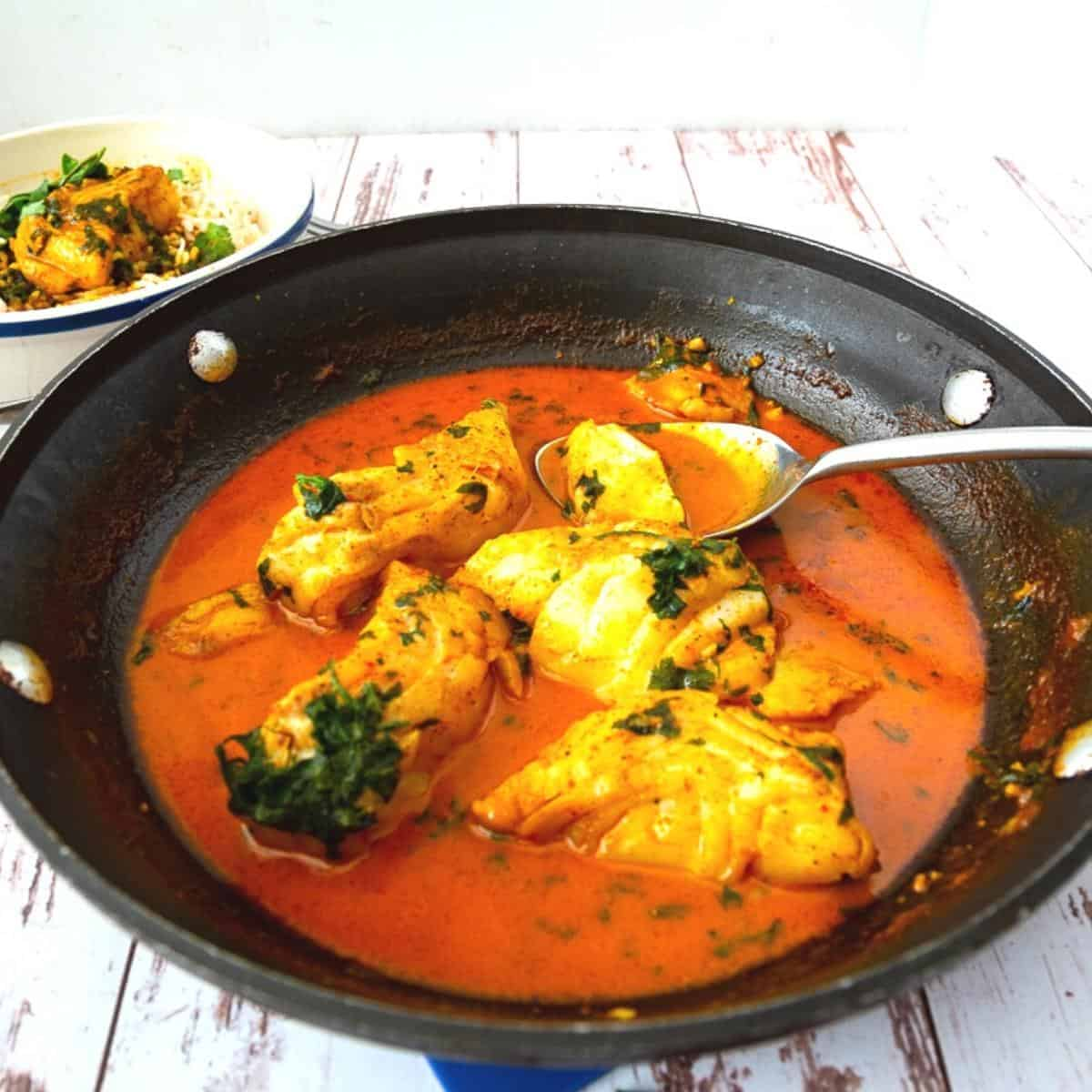 Red Fish curry in a skillet.