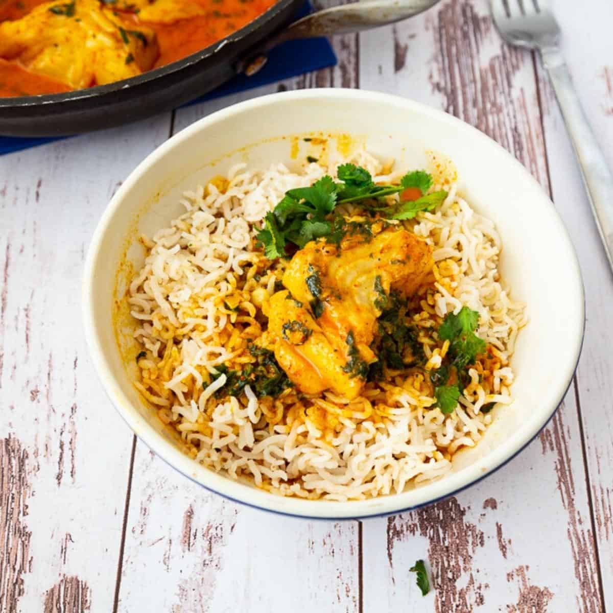 A bowl of rice topped with fish and curry.