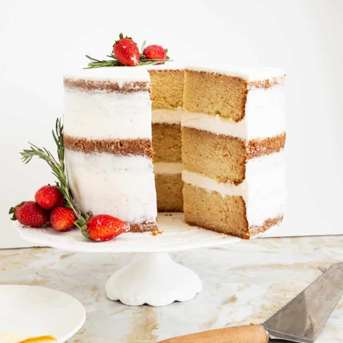 A sliced vanilla cake on the cake stand.