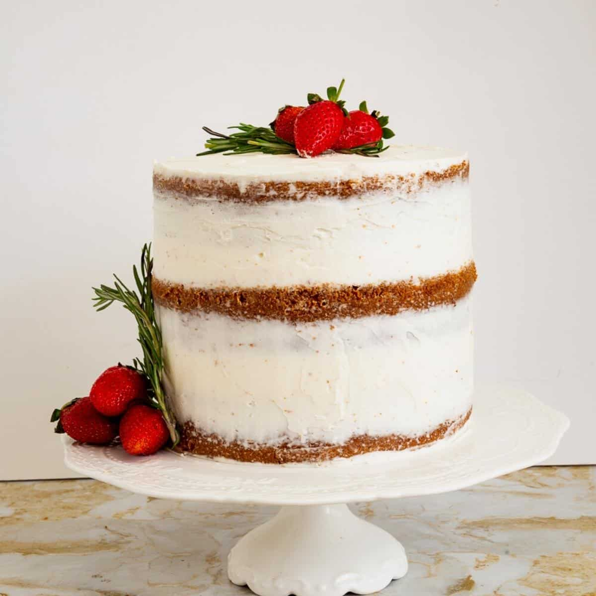 A naked vanilla cake on a cake stand with strawberries.